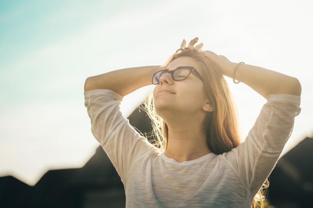 mujer con los brazos en la cabeza feliz por el efecto de la anandamida